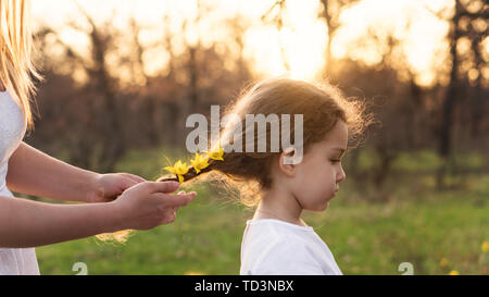 Caring motherly hands braid the hair of little girl. Mom adorns her hair by braiding live yellow forest flowers in pigtail. Happy motherhood. Child - Stock Image
