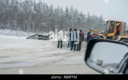 Russian winter, snowstorm on the road, dangerous driving, the car was thrown off the road - Stock Image