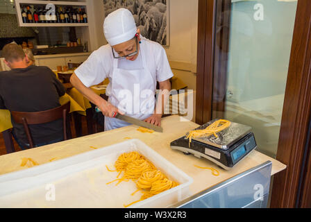 An Italian woman demonstrating the making of fresh pasta at restaurant, Rome, Italy - Stock Image