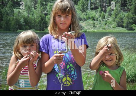 young girls snakes mountain lake stream snow spring reptile happy fun - Stock Image