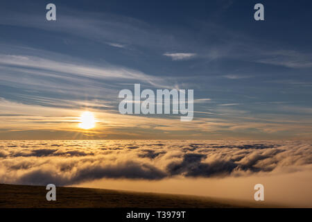 Beautiful sunset over a valley filled by fog with mountains and hills - Stock Image