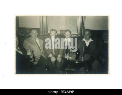 Vintage black and white photo of old army pals having a drink in a pub 1960s - Social History - Stock Image