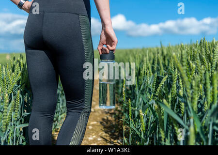 glass water bottle. Close up of a sporty woman carrying a water bottle. - Stock Image