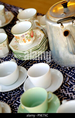 stacks of china tea cups and saucers and a metal kettle - Stock Image