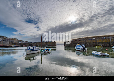 Mousehole, Cornwall, UK. 27th May 2019. UK Weather. Early morning sunshine breaking out behind high clouds for the start of bank holiday monday at Mousehole harbour. Credit Simon Maycock / Alamy Live News. - Stock Image