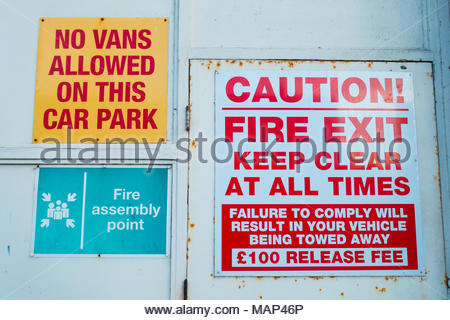 Three Signs on a white doorway, no vans allowed on this car park, caution! Fire Exit,keep clear at all times, failure to comply Southport, Merseyside - Stock Image