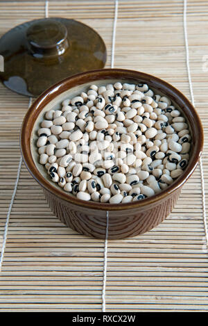 Black Eyed Beans in vintage brown pottery casserole dish with lid behind on placemat. - Stock Image