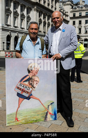 London, UK. 23 June 2018. Political artist Kaya Mar and Sir Vince Cable, Leader of the Liberal Democrats pose with Kaya Mar's painting 'Hard Brexit' which depicts Theresa May and Jeremy Corbyn walking off a cliff edge. Remain supporters and protesters gather in Pall Mall for an Anti-Brexit March and Rally. Photo: Bettina Strenske/Alamy Live News - Stock Image