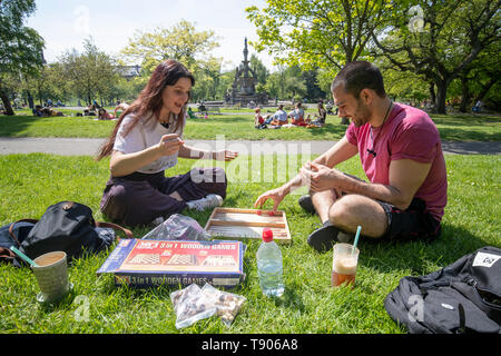 Students Iris Mandragouda (left) and Costas Spanachis enjoy the sunshine in Glasgow's Kelvingrove Park as the hot weather continues. - Stock Image