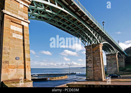 The view from South Bay all the way to Filey Brigg, seen through the arches of  Scarborough's Spa Bridge as it spans the end of Valley Road. - Stock Image