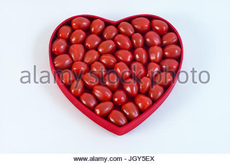 Cherry tomatoes in heart shaped plate against white background - Stock Image