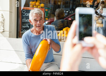 Netherlands, Amsterdam, cell phone picture of senior man sitting on bench holding loaf of cheese - Stock Image