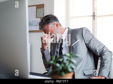 A frustrated businessman sitting at the desk in an office, hearing bad news. - Stock Image