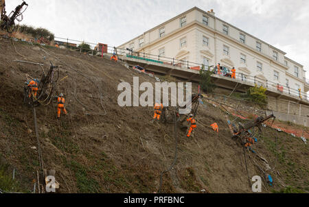 Construction engineers working in harnesses supported by cables working on cliff face at Scarborough. unsharpened - Stock Image