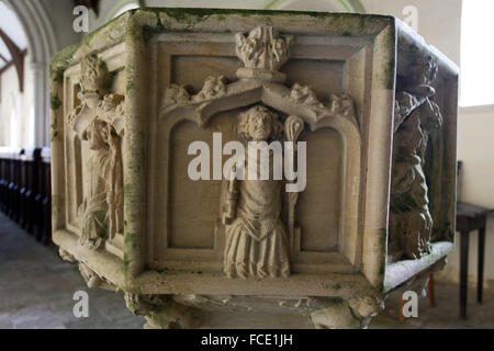 Detail from the 15th century stone font with carvings of the apostles, St Nicholas Church, Buckenaham - Stock Image