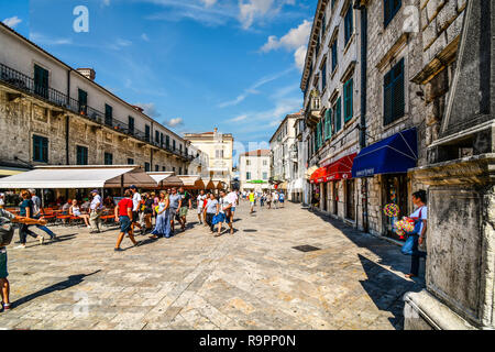 A woman selling souvenirs takes a cigarette break in the shade in the Piazza of the Arms in the ancient city of Kotor, Montenegro as tourists pass by - Stock Image
