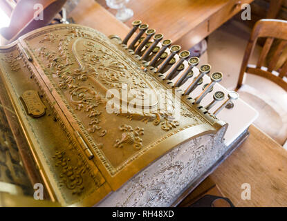 Old Manual decorated Cash register: Cast in solid metal this highly decorated cash register and it levers is part of a museum display. - Stock Image