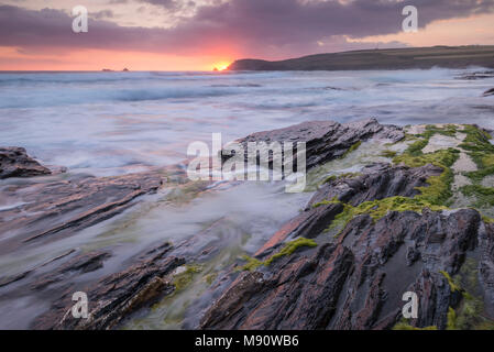 Waves crash against the rocky shores of Booby's Bay at sunset, Cornwall, England. Summer (July) 2017. - Stock Image