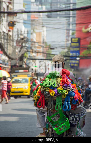 A Vietnamese trader drives along the street looking to sell his colourful products. - Stock Image
