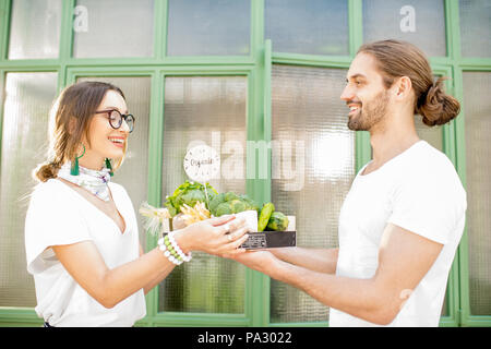 Man delivering to the woman client fresh vegetables standing together near the entrance outdoors - Stock Image