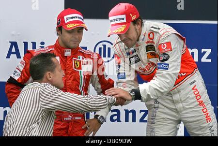 Former Formula One champion Michael Schumacher (L) congratulates Spanish winner Fernando Alonso of McLaren Mercedes - Stock Image