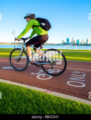 Male cyclist riding down a cycle only bike path / cycle lane with Perth city skyline in the distance - Stock Image