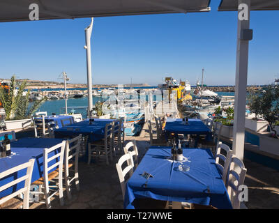 Inviting free tables and a sunny view, ready for lunch in the harbour of Ayia Napa Cyprus - Stock Image