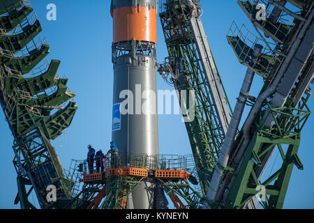 Workers are seen on a gantry as the service structure arms are raised around the Soyuz rocket, Friday, Dec. 15, - Stock Image
