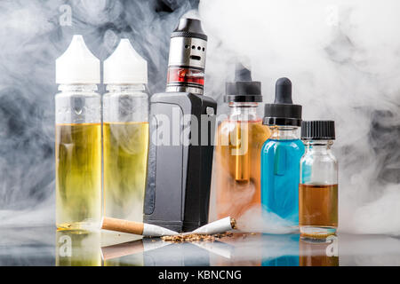 Modern vaporiser versus old tobacco cigarette in smoke cloud - Stock Image
