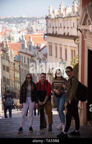 Young traveling people standing on the street. Men holding shooting equipment. Mid shot - Stock Image