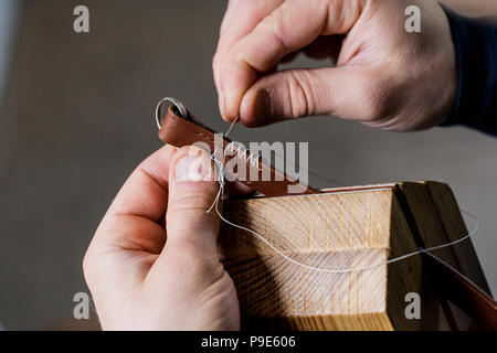 Close up of craftsman making brown leather camera strap, hand stitching two pieces of leather, held in a clamp. - Stock Image