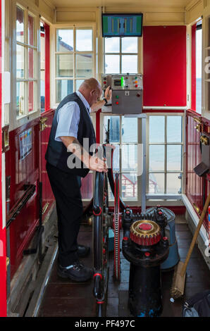 Saltburn cliff lift operator at the top station waiting for a signal from the bottom station to operate the lift - Stock Image
