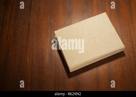 Beige color book on the wooden scratched table - Stock Image