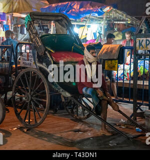 Square portrait a pulled rickshaw owner waiting for business in Kolkata aka Calcutta, India. - Stock Image