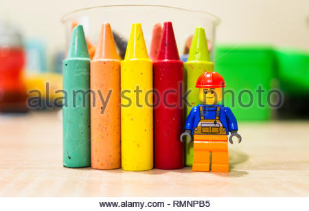 Poznan, Poland - February 13, 2019: Lego construction worker standing next to a colorful set of crayons on a wooden table in soft focus background. - Stock Image