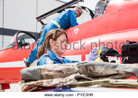 Woman cleaning helmet by Red Arrows airplane on RAF Scrampton, UK - Stock Image