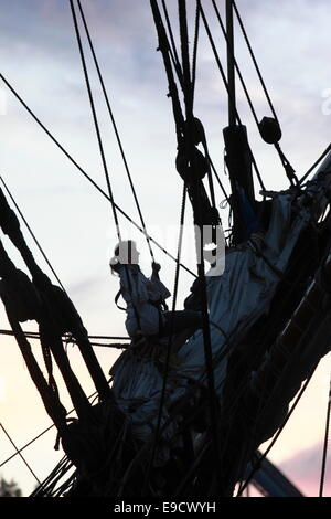Young woman climbing in the rigging of a tall ship. - Stock Image