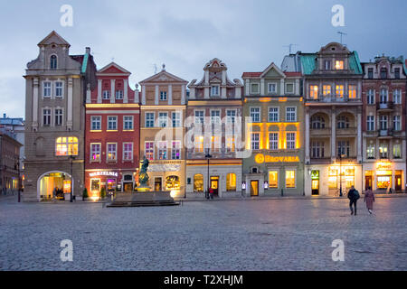 Evening low light nighttime dusk in the old town square in the Polish city of Poznan Poland with its brightly coloured houses restaurants and cafes - Stock Image