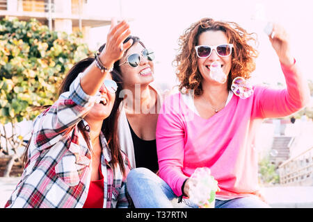 friendship people concept with group of three young caucasian woman together having fun in playful outdoor leisure activity playing and laughing with  - Stock Image