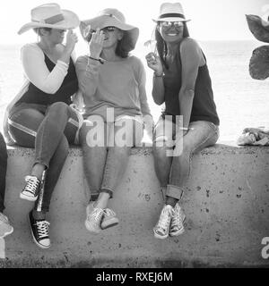 Black and white summer concept image with three middle age young woman laughing and enjoying together the friendship and the outdoor lifestyle - vacat - Stock Image