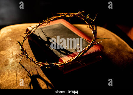 Sunlight hits a Christian Bible and a communion cup filled with grape juice and a crown of thorns representing Christ's crucifixion. - Stock Image