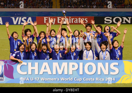 Japan squad in National Stadium pitch, posing with Champions medals and trophy. - Stock Image
