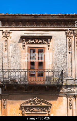 Typical traditional Sicilian architecture balcony, shutters and ornate stonework in Piazza San Giovanni in Ragusa Ibla, Sicily - Stock Image