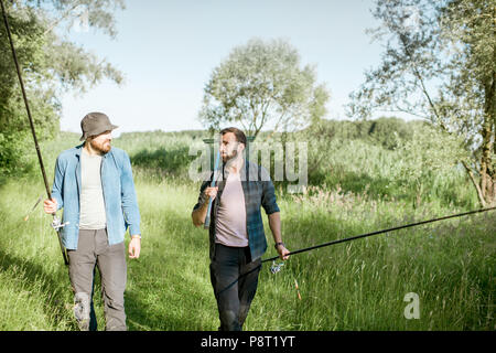 Two fishermen walking with fishing rod and net on the green lawn near the lake in the morning - Stock Image