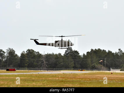 Old military helicopoter takes off over green field - Stock Image