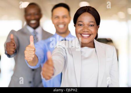 professional vehicle sales team in a row giving thumbs up - Stock Image
