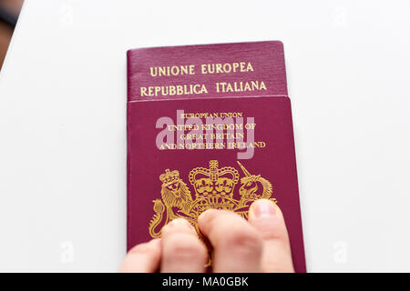 British passport stacked on top of Italian passport on white surface. Male fingertips pushing passport forward. - Stock Image