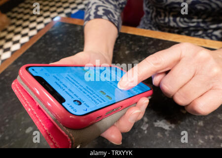 Hands holding a pink apple iphone with finger pointing to an entered text message on the apple screen - Stock Image