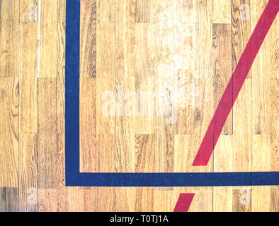 Hall floor in a gymnasium with diverse lines. Worn out wooden floor of sports hall with colorful marking lines. Schooll gym hall - Stock Image