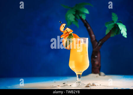 Decorated yellow tropical cocktail in a tulip glass with oranges on a skewer. Papercraft palm trees on a blue background with copy space. - Stock Image